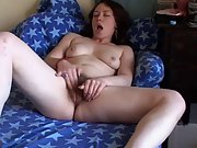 Pale and dark haired babe fingers her hairy pussy on sofa